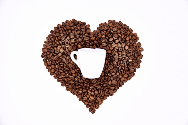 Heart of coffee beans and a white cup. Premium Photo