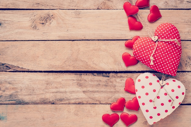 Heart fabric frame on wooden table background. Premium Photo
