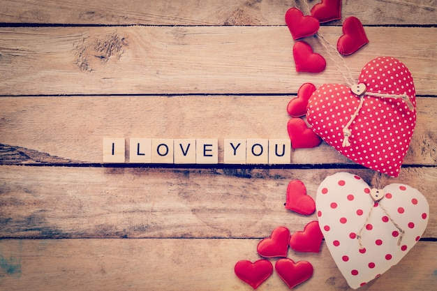 Heart fabric frame and wooden text i love you on wooden table background. Premium Photo