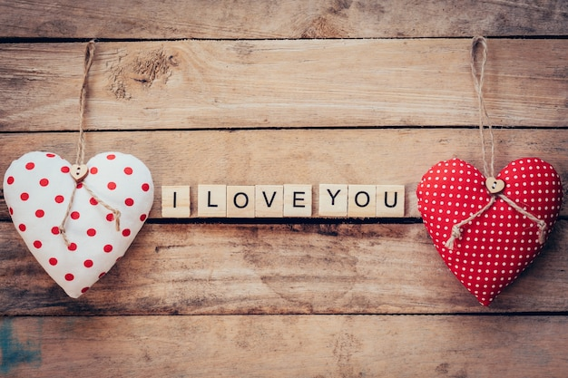 Heart fabric and wooden text i love you on wooden table background. Premium Photo