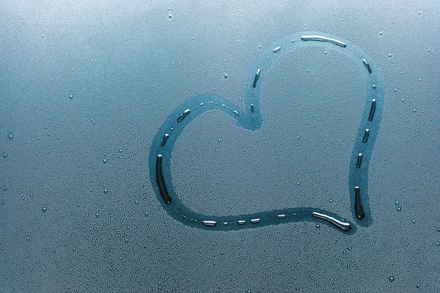 Heart on the glass and drops of water. Premium Photo