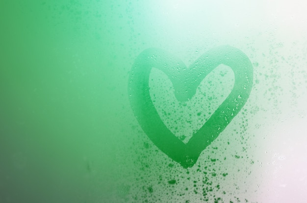The heart is painted on the misted glass in the winter Premium Photo