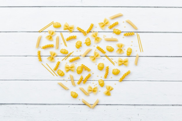 Heart made by different types of pasta on wooden table Free Photo