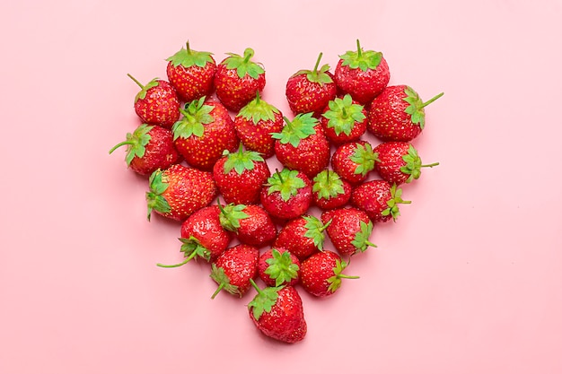 Heart made from deluxe, natural juicy strawberry on trend pink background Premium Photo