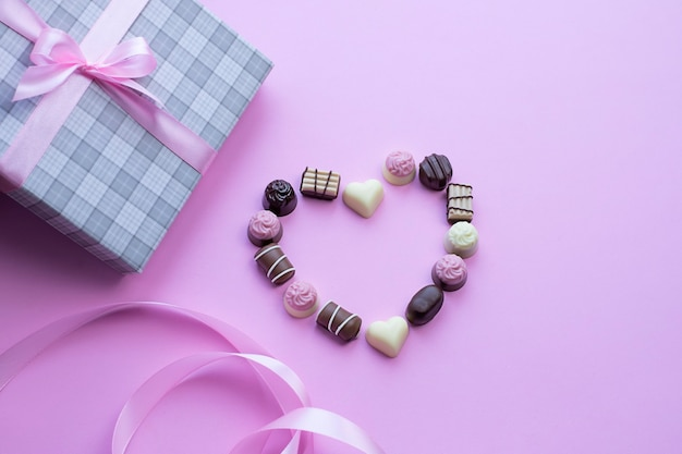 Сердце из шоколадных конфет на розовом фоне изображение с копией пространства Premium Фотографии