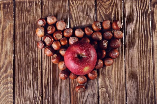 木製のテーブルの上のナッツとリンゴで作られた心、中心部のリンゴに焦点を当てる Premium写真