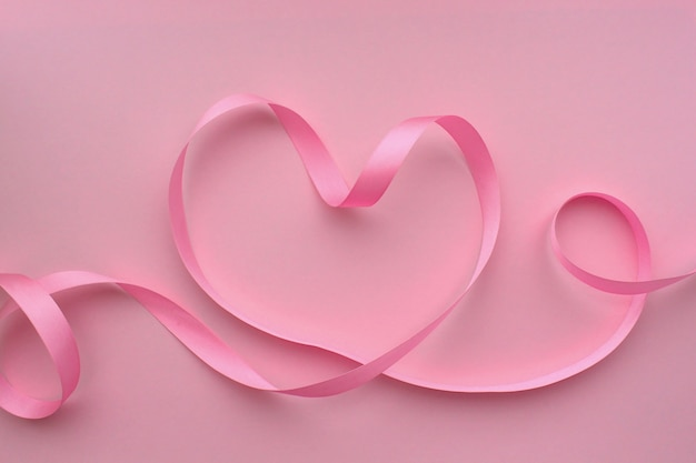 핑크 바탕에 핑크 리본으로 만든 심장 프리미엄 사진