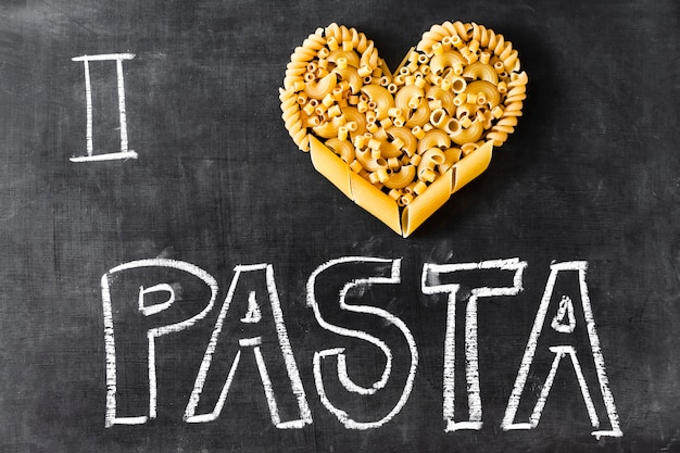 Heart made with different type of pasta and text on blackboard Free Photo