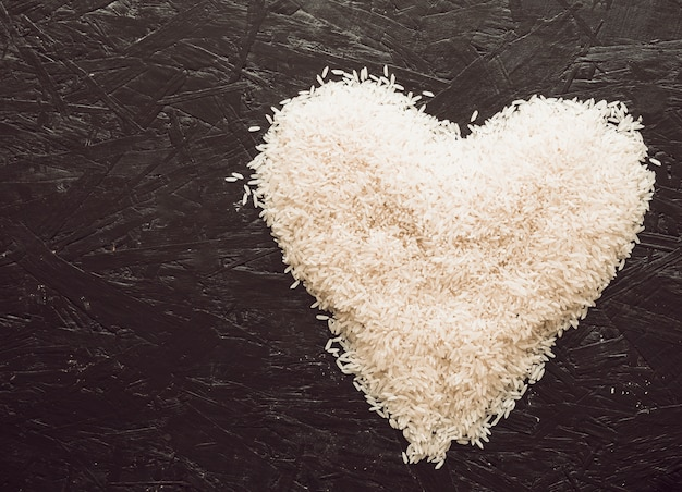 Heart made with rice grains on textured background Free Photo