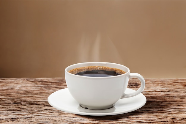 Сердце пара парит над красной чашкой кофе на деревянном столе с кремовой стеной Premium Фотографии