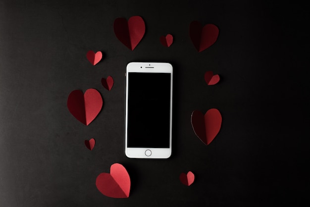 Heart and phone on black wall background Free Photo