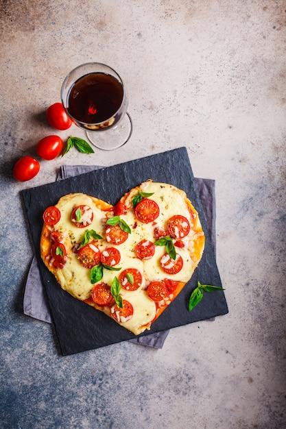 モッツァレラチーズとトマトのスレートとワインのハートピザ Premium写真