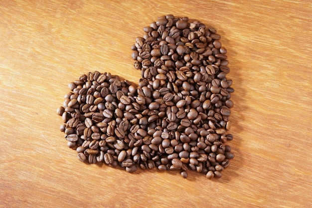 Heart roasted coffee beans on wooden background Premium Photo