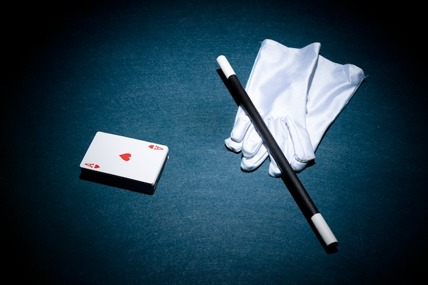 Heart shape aces card; magic wand and white pair of gloves over poker table Free Photo