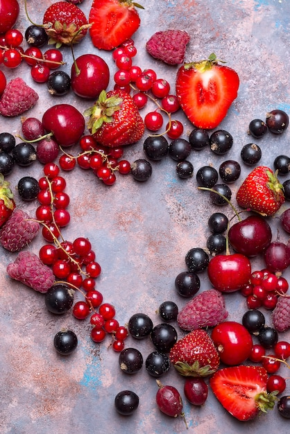 Heart shape assorted berry fruits on stone background. flat lay Premium Photo