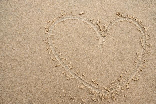 Heart shape on the beach sand background. Premium Photo