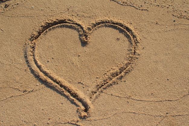 ビーチの砂に描かれたハート Premium写真