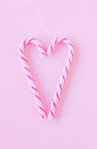 Heart shape from candy canes on table Free Photo