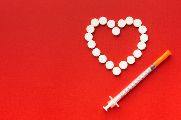 Heart shape from pills and syringe Free Photo