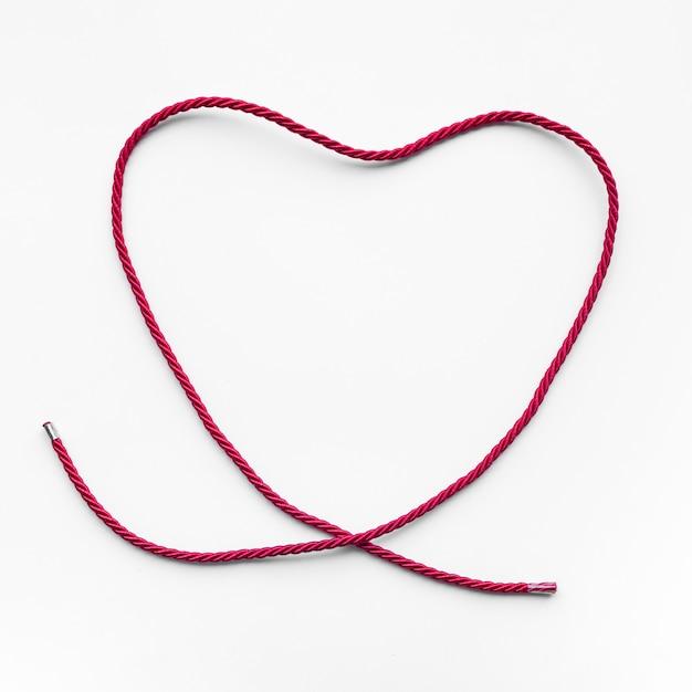 Форма сердца из красной пряжи, веревка на синем фоне. Premium Фотографии