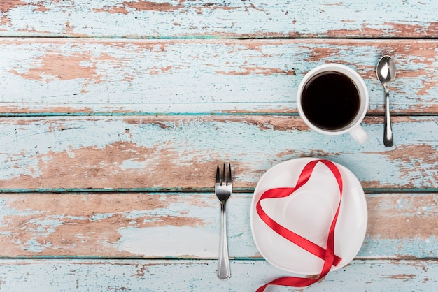 Heart shape from ribbon on plate with coffee Free Photo