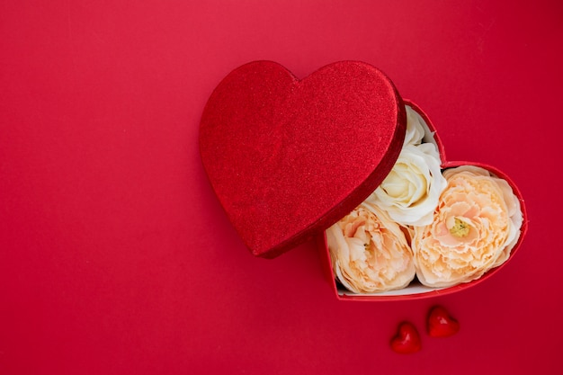 Heart shape gift box with flowers on red backgroun. valentine's day mock up with copy space. Premium Photo