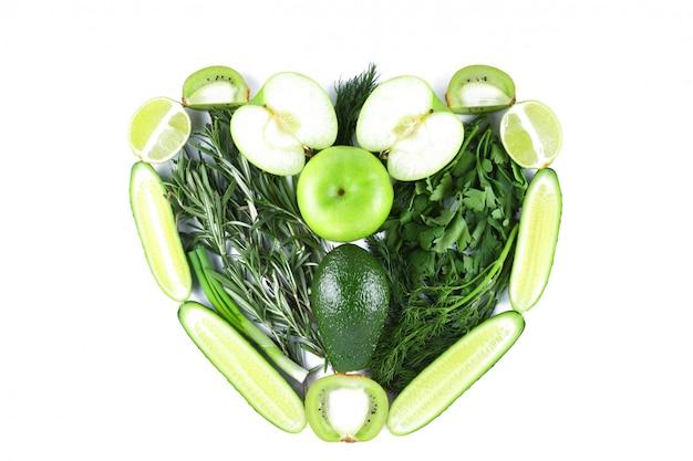 Форма сердца из зеленых фруктов и овощей. сердце из натуральных продуктов на белом фоне. изолированное вегетарианское сердце Premium Фотографии