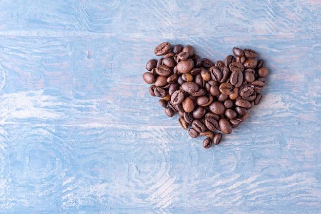 Форма сердца из кофейных зерен на синем стильном деревянном фоне Premium Фотографии