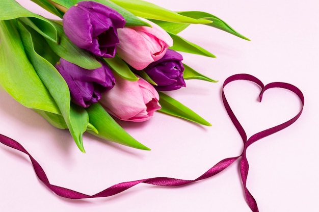 Heart shape made of purple ribbon and bouquet of purple and pink tulips on a light pink background Premium Photo
