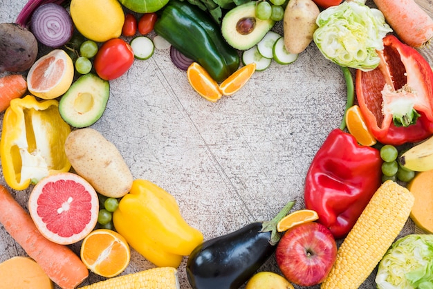 Heart shape made with colorful vegetables on textured backdrop Free Photo