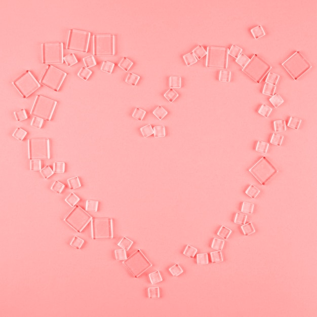 Heart shape made with different type of transparent cubes on coral background Free Photo