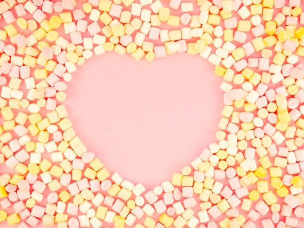 Heart shape surrounded by candy Free Photo