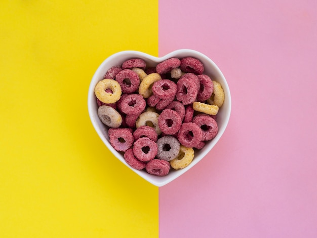 Heart shaped bowl filled with pink and yellow fruit loops Free Photo