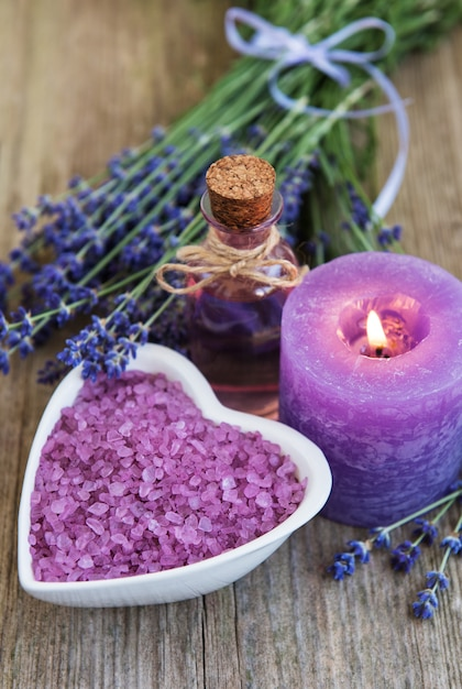 Heart-shaped bowl with sea salt and fresh lavender flowers on a old wooden table Premium Photo