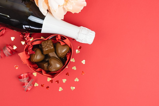Heart shaped box with chocolates and champagne bottle on a red background. valentine day Premium Photo