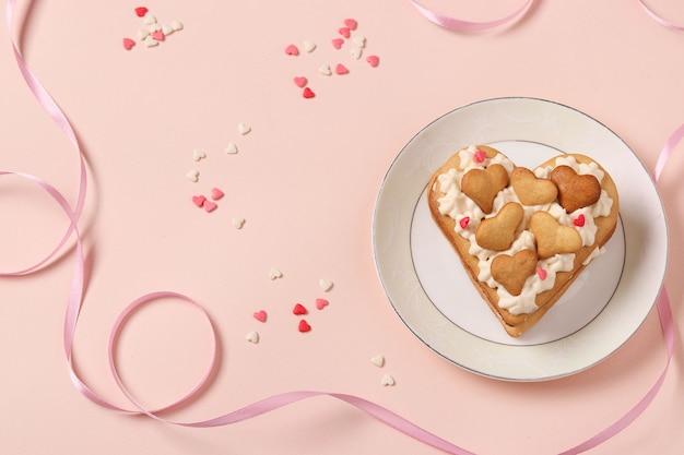 Торт в форме сердца на розовом фоне на день всех влюбленных Premium Фотографии