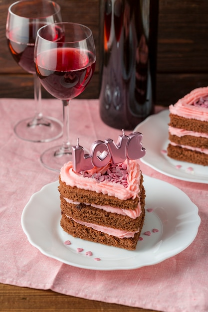 Heart-shaped cake slice with wine glasses and candles Free Photo