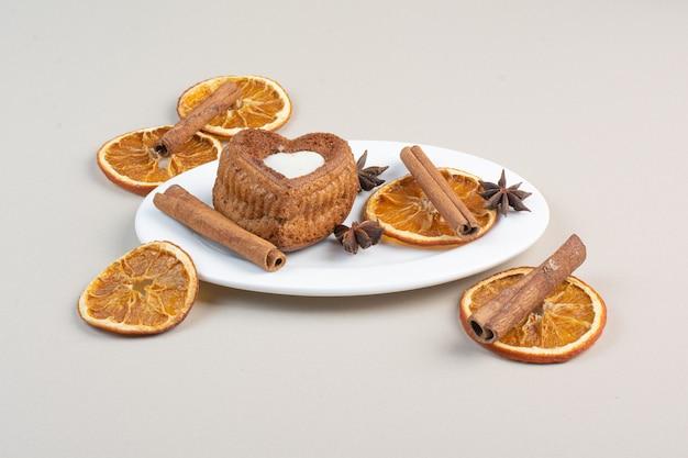 白いプレートにオレンジスライス、クローブ、シナモンとハート型のケーキ 無料写真