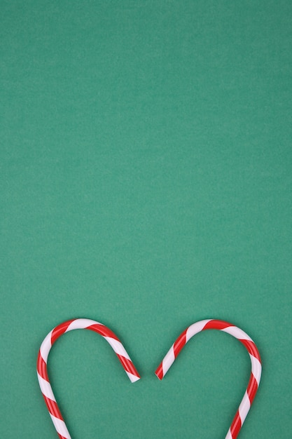 Heart-shaped cane candy on green background Premium Photo