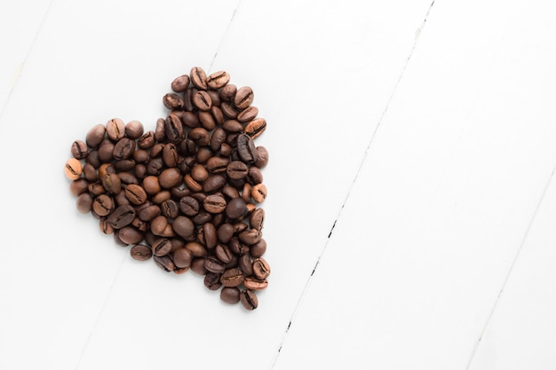 Heart-shaped coffee grains on white wooden background Premium Photo