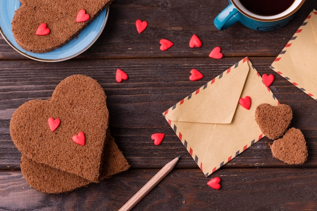 Heart-shaped cookies with sprinkles and envelope Free Photo