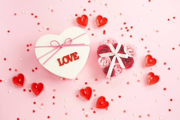 Heart shaped gift box, gift , candle, confetti on pink. Premium Photo