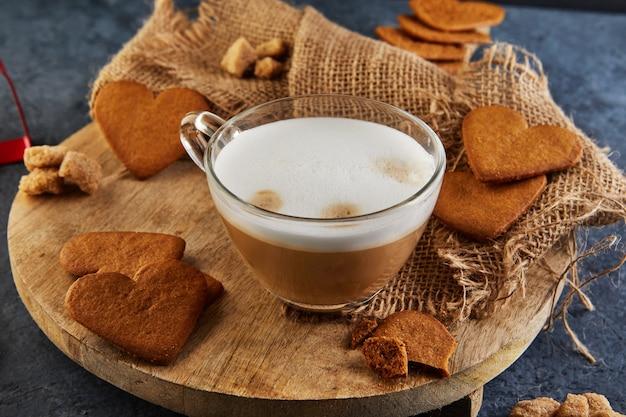 木の板にカプチーノコーヒーを入れたハート型のジンジャーブレッドクッキー。 Premium写真