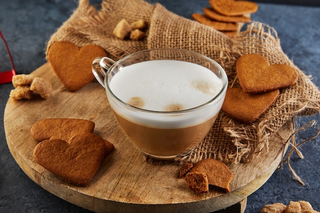 Heart shaped gingerbread cookies with a cup of cappuccino coffee on a wooden board. Premium Photo