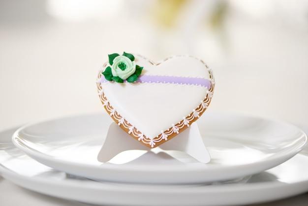 Глазированное печенье в форме сердца - украшенное зеленым глазурным цветком и мелким узором стоит на белых тарелках как украшение праздничного свадебного стола. печенье стоит на белом ресторане Бесплатные Фотографии