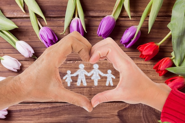 Heart-shaped hands around a family Free Photo