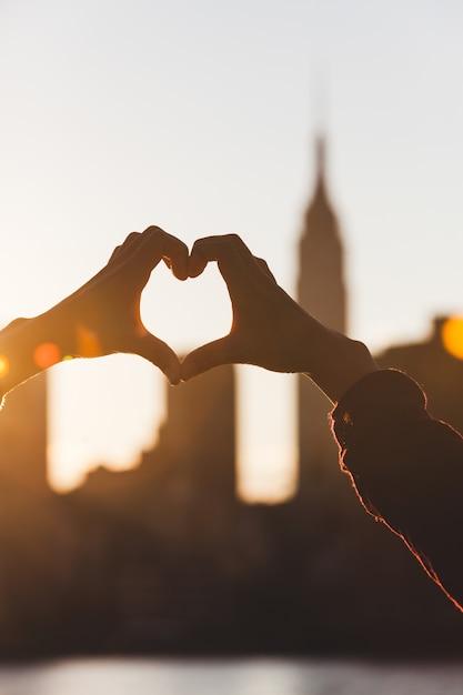 Heart shaped hands at sunset, new york skyline Premium Photo