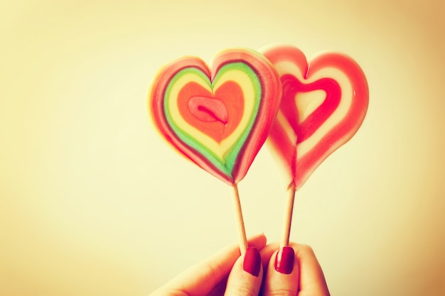 Heart-shaped lollipop held by a hand Free Photo