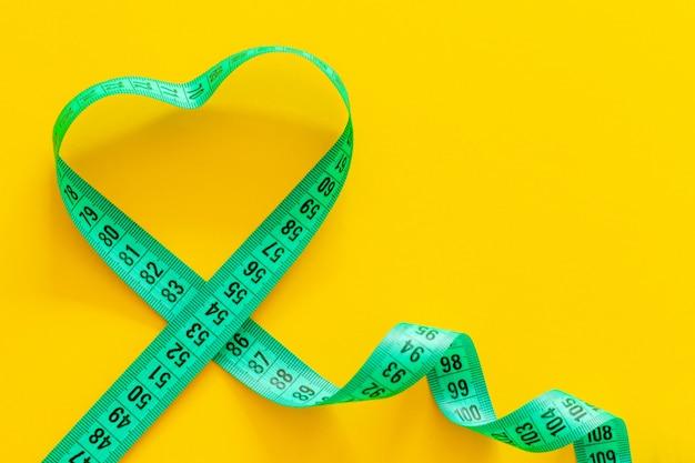 Heart shaped measure tape on yellow background Premium Photo