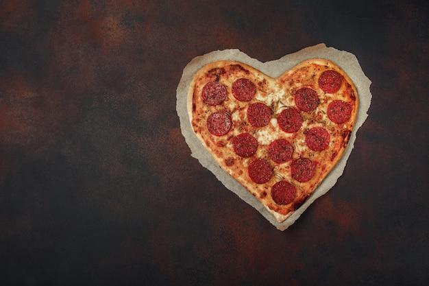 Heart shaped pizza with mozzarella and sausage. Premium Photo